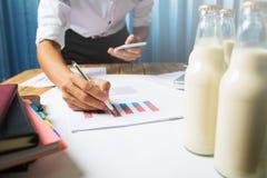 Affärsmannen som arbetar på, mjölkar kvalitets- kontroll för flaska som det hårda jobbet lurar royaltyfri foto