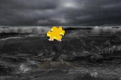Affärsmannen som bär det guld- pusslet 3D vaggar på, i det mörka havet Arkivfoton