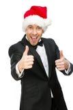 Affärsmannen som bär det Santa Claus locket, tummar upp royaltyfria bilder