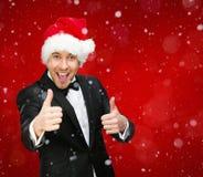 Affärsmannen som bär det Santa Claus locket, tummar upp arkivfoto
