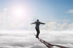 Affärsmannen som balanserar på gammal järnkedja med himmelsolljus, fördunklar Royaltyfri Bild