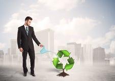 Affärsmannen som bevattnar gräsplan, återanvänder teckenträdet på stadsbakgrund Arkivfoton