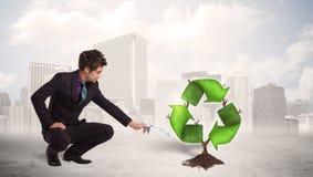 Affärsmannen som bevattnar gräsplan, återanvänder teckenträdet på stadsbakgrund royaltyfri foto