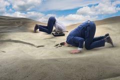 Affärsmannen som döljer hans huvud i sand som flyr från problem arkivbild