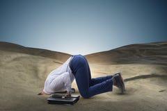 Affärsmannen som döljer hans huvud i sand som flyr från problem royaltyfri foto