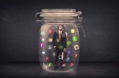Affärsmannen som fångas i en glass krus med färgglade app-symboler, lurar Royaltyfri Bild