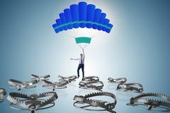 Affärsmannen som faller in i fälla hoppa fallskärm på Arkivfoton