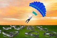 Affärsmannen som faller in i fälla hoppa fallskärm på Royaltyfria Foton