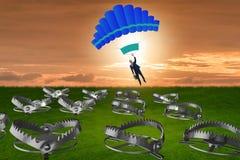 Affärsmannen som faller in i fälla hoppa fallskärm på Royaltyfria Bilder