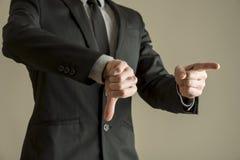 Affärsmannen som ger en negation för tummar, röstar ner royaltyfri foto