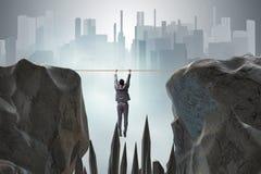 Affärsmannen som hänger på rep i farabegrepp arkivfoton