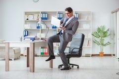 Affärsmannen som har gyckel som tar ett avbrott i kontoret på arbete royaltyfria foton