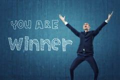Affärsmannen som hoppar lyckligt med hans armar upp near ord` är du, vinnare` som är skriftlig på mörker - blå vägg Royaltyfri Foto