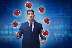 Affärsmannen som jonglerar med piggybanks i affärsidé Arkivbild