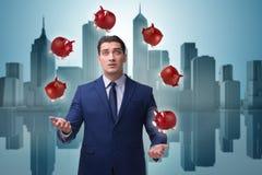 Affärsmannen som jonglerar med piggybanks i affärsidé Fotografering för Bildbyråer