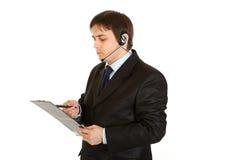affärsmannen som kontrollerar hörlurar med mikrofon, bemärker allvarligt Arkivfoto