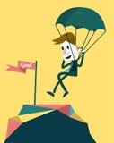 Affärsmannen som landar till målet med, hoppa fallskärm. Arkivfoto