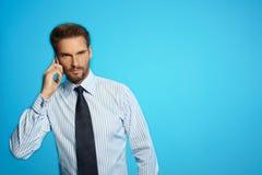 Affärsmannen som meddelar på telefonen som står över blått, isolerade bakgrund Royaltyfria Foton