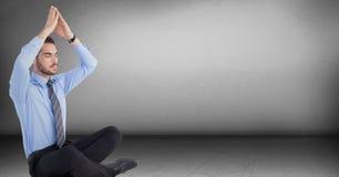 Affärsmannen som mediterar med handen som är över huvudet i grå färger, hyr rum Fotografering för Bildbyråer