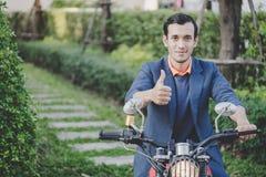 Affärsmannen som rider en moped i, parkerar royaltyfria foton