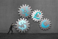 Affärsmannen som rullar ett stort konkret kugghjul, förbinder med andra Arkivbild