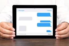 Affärsmannen som rymmer en minnestavladator med sms, pratar på en skärm arkivbild