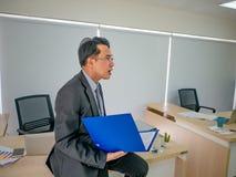 Affärsmannen som rymmer hans dokument, sitter på tabellen arkivbilder