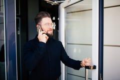 Affärsmannen som rymmer kontorsdörren och, får utomhus- vit talar på telefonen Mannen får ut utgången från kontorsbyggnad fotografering för bildbyråer