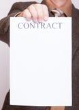 Affärsmannen som rymmer tomt papper med, undertecknar avtalet Royaltyfri Foto