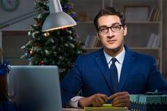Affärsmannen som sent i regeringsställning arbetar på juldag Royaltyfri Bild