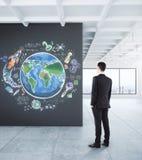 Affärsmannen som ser jordklotet, skissar Arkivfoto
