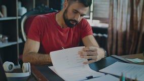 Affärsmannen som sist undertecknar avtalet i slut av dagen och kastar, skyler över brister till skrivbordet arkivfilmer