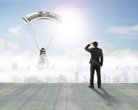 Affärsmannen som stirrar den ljusa kulan med pengar, hoppa fallskärm Royaltyfria Foton