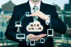 Affärsmannen som trycker på ett moln, förband till många objekt på en faktisk skärm, begrepp om internet av saker Royaltyfri Bild