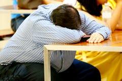 Affärsmannen sover på skrivbordet efter överansträngt trött royaltyfria bilder