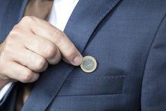 Affärsmannen sparar varje monete Arkivbild
