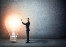 Affärsmannen står den rörande stora glödande ljusa kulan Arkivfoton