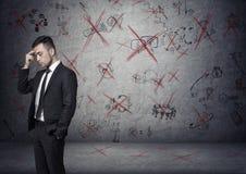 Affärsmannen står grubbla på den konkreta bakgrunden med visade idéer som korsade vid rött Arkivfoton