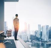 Affärsmannen står, i modernt kontor och att se staden fyrkant royaltyfri fotografi