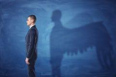 Affärsmannen står i profil, och gjuta en skugga av ängeln påskyndar på blå svart tavlabakgrund royaltyfri bild