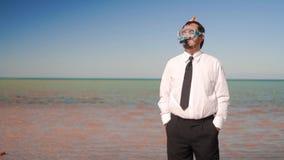 Aff?rsmannen st?r p? stranden i en maskering och en snorkel stock video