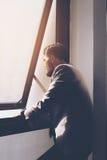 Affärsmannen tänker framme av ett fönster Royaltyfria Foton
