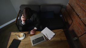 Affärsmannen talar på smartphonen i kafé och arbetar med affärslegitimationshandlingar Mannen sitter på tabellen i kafé och talar arkivfilmer