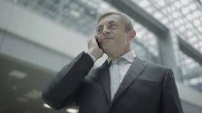 Affärsmannen talar på telefonen i flygplatsen stock video