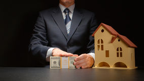 Affärsmannen trycker på en pengarbunt nära en husmodell på tabellen Arkivbild