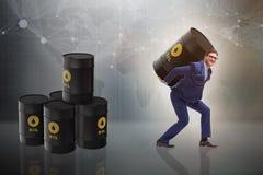 Affärsmannen under bördan av den olje- trumman Arkivbilder