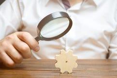 Affärsmannen undersöker ett träkugghjul till och med ett förstoringsglas studie och analys av affärsprocessar och ämnen royaltyfria foton