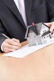 Affärsmannen undertecknar avtalet bak hus arkivfoton