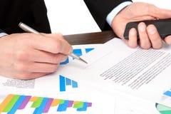 Affärsmannen undertecknar ett dokument på kontoret och håller telefonen Arkivbilder