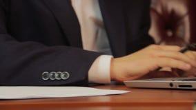Affärsmannen undertecknar legitimationshandlingar, avtalet, överenskommelse, arbeten på bärbara datorn stock video